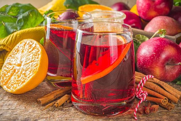 Tradycyjny napój alkoholowy jesień zima. sangria owocowa gorąca jesień z cytrusami, jabłkami i przyprawami, rustykalne drewniane tła