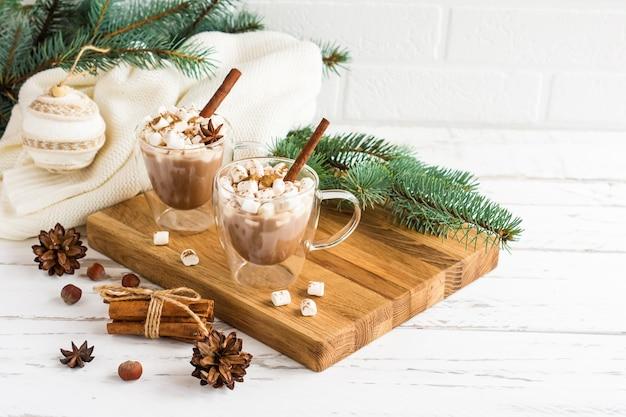 Tradycyjny napój noworoczny z pianką marshmallow na drewnianej desce na tle białej ściany z cegły, świerkowych gałęzi i świątecznych zabawek.