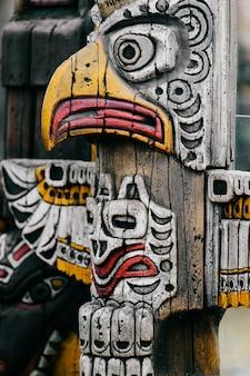 Tradycyjny narodowy indyjski totem. sztuka rzeźby z totemu. starożytna drewniana maska. twarze symbolicznych bogów religijnych majów i azteków.
