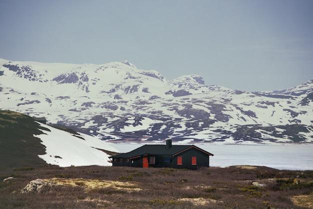 Tradycyjny norweski drewniany dom do postawienia nad jeziorem i górami w oddali, norwegia