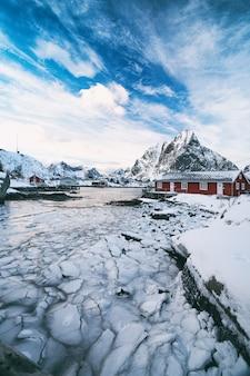Tradycyjny norweski drewniany dom rorbu do stania na brzegu fiordu i gór w oddali. lofoty. norwegia. podróż po świecie