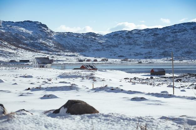Tradycyjny norweski drewniany dom stoją na brzegu fiordu i gór w oddali. lofoty. norwegia. podróż po świecie