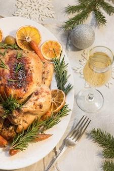Tradycyjny pieczony indyk z rozmarynem i lampką szampana na świątecznym stole.
