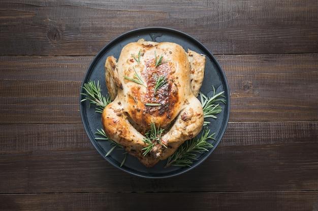 Tradycyjny pieczony kurczak z rozmarynem na drewnianym stole. widok z góry.
