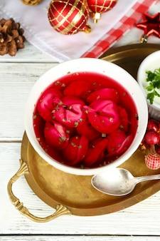 Tradycyjny polski barszcz jasnoczerwony z kluskami w misce na tacy i ozdobami świątecznymi