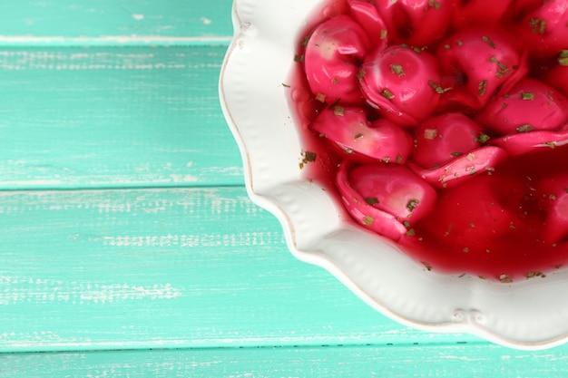 Tradycyjny polski jasnoczerwony barszcz z kluskami na kolorowej drewnianej powierzchni