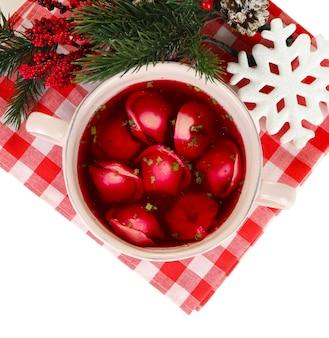 Tradycyjny polski jasny barszcz czerwony z kluskami i ozdobami świątecznymi na białym tle