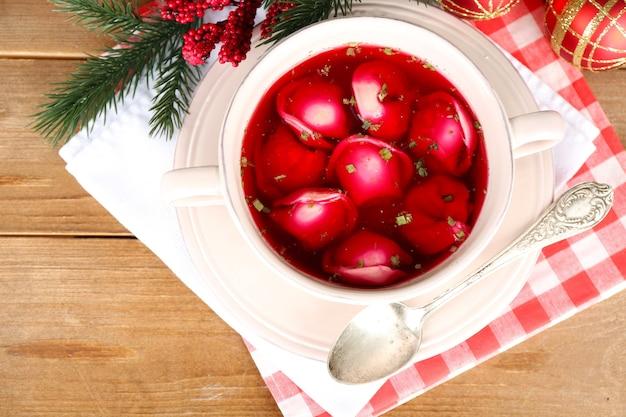 Tradycyjny polski jasny barszcz czerwony z kluskami i ozdobami świątecznymi na drewnianej powierzchni stołu