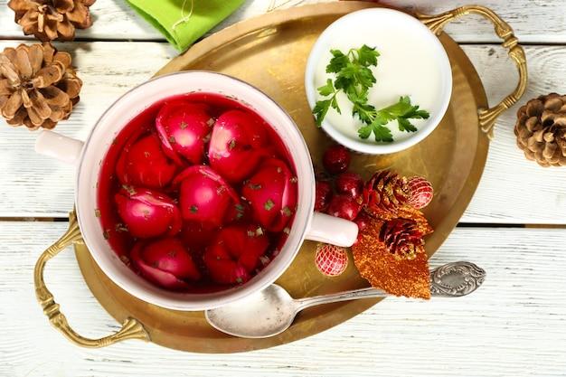 Tradycyjny polski jasny barszcz czerwony z kluskami i ozdobami świątecznymi na drewnianym tle