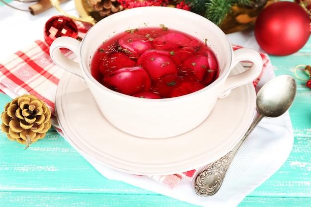 Tradycyjny polski jasny barszcz czerwony z kluskami i ozdobami świątecznymi na kolorowej drewnianej powierzchni stołu