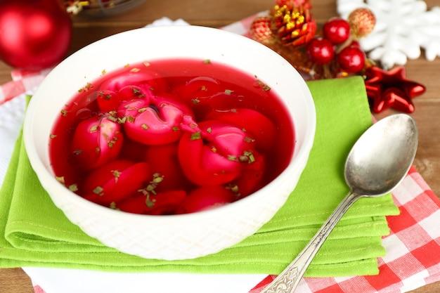 Tradycyjny polski jasny barszcz czerwony z kluskami i ozdobami świątecznymi na tle drewnianego stołu