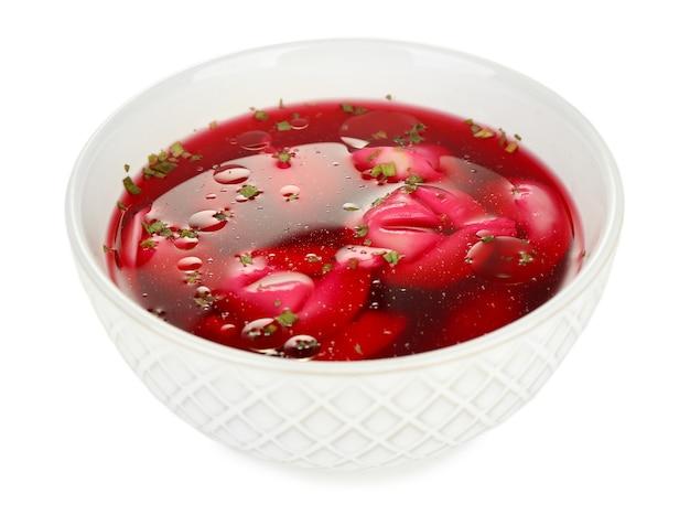 Tradycyjny polski jasny barszcz czerwony z kluskami na białym tle