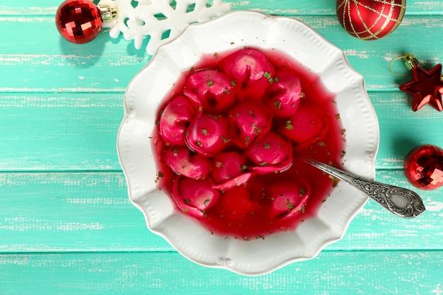 Tradycyjny polski jasny barszcz czerwony z kluskami na kolorowym drewnianym stole