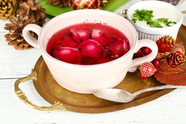 Tradycyjny polski jasny barszcz czerwony z kluskami w misce na tacy i ozdobami świątecznymi na drewnianej powierzchni