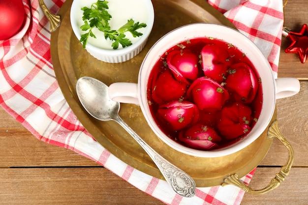 Tradycyjny polski jasny barszcz czerwony z kluskami w misce na tacy i ozdoby świąteczne na drewnianym tle