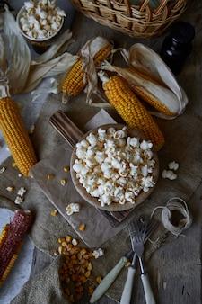 Tradycyjny popcorn w drewnianej misce i kaczany kukurydzy na stole.