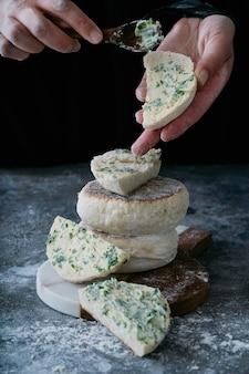 Tradycyjny portugalski płaski okrągły chleb bolo do caco. kobiece ręce masło chleb. selektywna ostrość