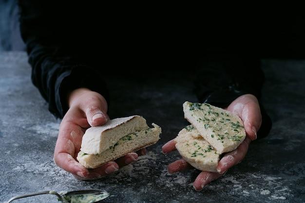 Tradycyjny portugalski płaski okrągły chleb bolo do caco. kobiece ręce trzymając masłem kawałki chleba. selektywna ostrość