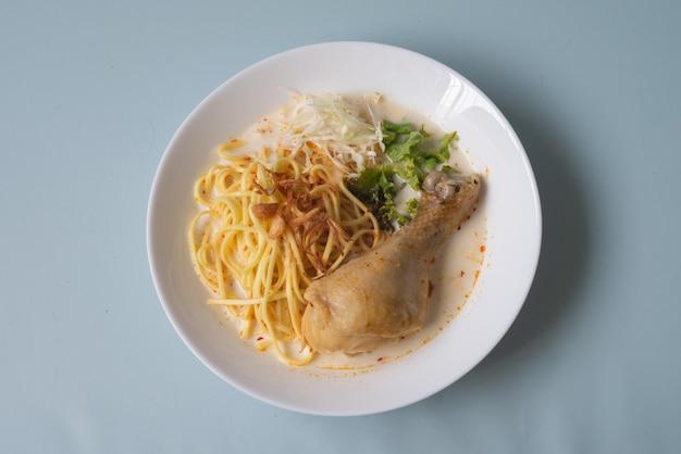 Tradycyjny posiłek azjatycki pikantna zupa z białej pasty curry z makaronem laksa z kurczakiem i warzywami z tajlandii, malezji lub singapuru