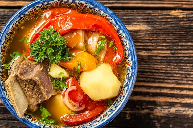 Tradycyjny posiłek uzbecki zupa shurpa z wołowiną i warzywami, na talerzu z orientalnym ornamentem