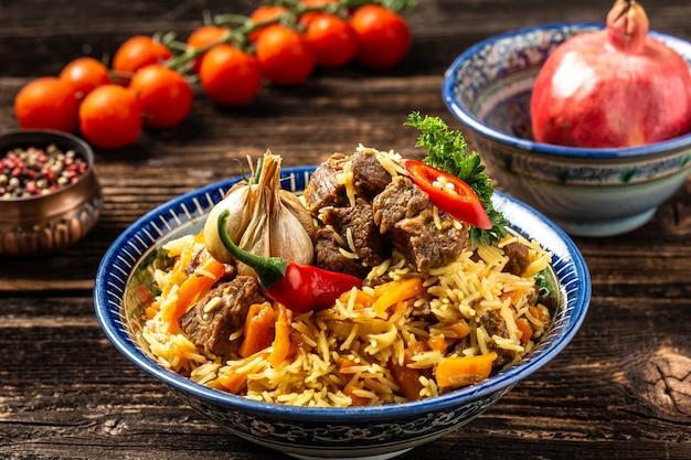 Tradycyjny posiłek uzbecki zwany pilawem. ryż z mięsem, marchewką i cebulą na talerzu z orientalnym ornamentem, orientalna kuchnia uzbecka. format długiego banera. miejsce na tekst.