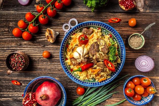 Tradycyjny posiłek uzbecki zwany pilawem. ryż z mięsem, marchewką i cebulą na talerzu z orientalnym ornamentem, orientalna kuchnia uzbecka. widok z góry.