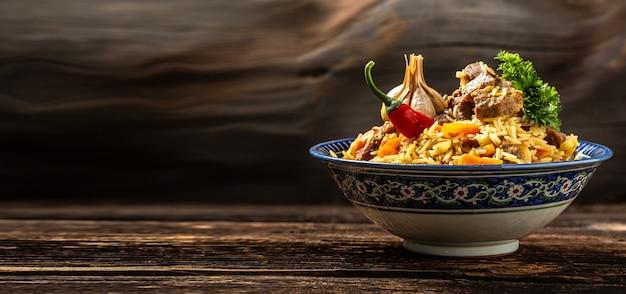 Tradycyjny posiłek uzbecki zwany pilawem. ryż z mięsem na talerzu z orientalnym ornamentem na ciemnym tle drewnianych, format długi baner. miejsce na tekst.