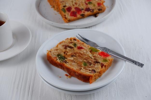 Tradycyjny pudding tort owocowy z suszonymi owocami na białym tle