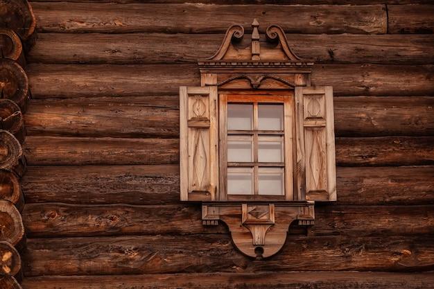 Tradycyjny rosyjski drewniany dom z bali z rzeźbionymi okiennicami