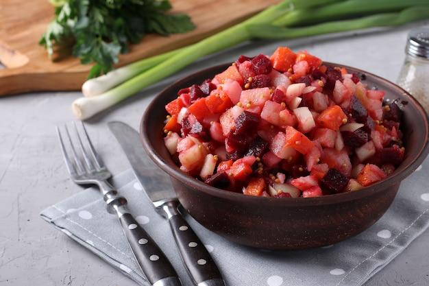 Tradycyjny rosyjski sos winegret z burakami, marchewką, ziemniakami i cebulą w glinianej misce