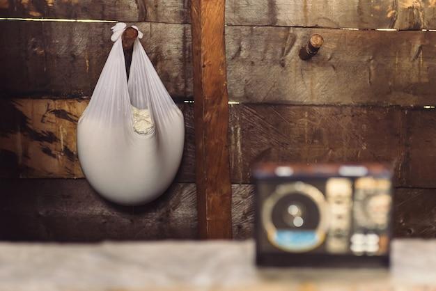 Tradycyjny ser wyrabiany w autentyczny sposób w drewnianej górskiej chacie. suszenie sera w białej gazie. karpaty, ukraina