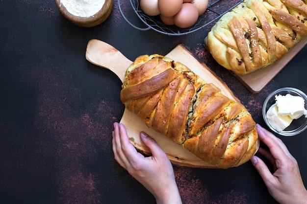 Tradycyjny słony placek kuchni rosyjskiej zwany kulebyaka. składniki na ciasto masło, mąka, jajka. ciemne tło rustykalne. widok z góry