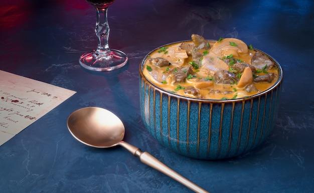 Tradycyjny stroganow wołowy z kremem z pieczarek w niebieskiej misce w restauracji.