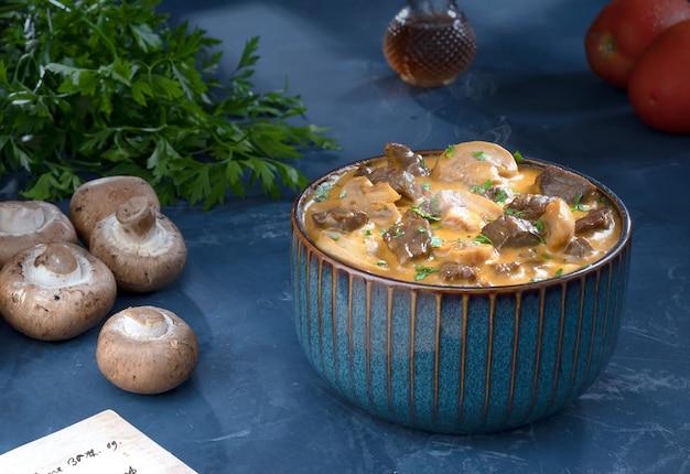 Tradycyjny stroganow wołowy z kremem z pieczarek w niebieskiej misce ze składnikami.