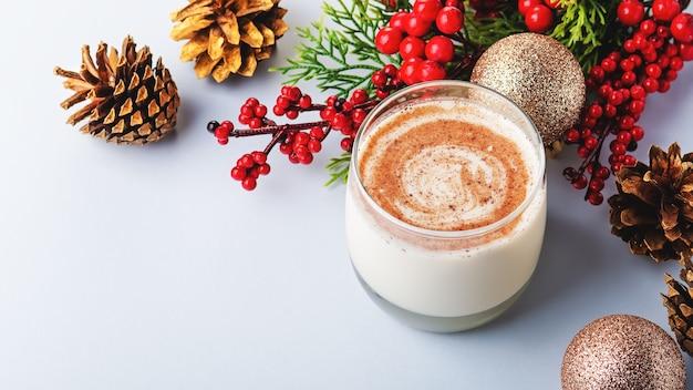 Tradycyjny świąteczny koktajl ajerkoniak z jajkiem alkohol starta gałka muszkatołowa i cynamon zbliżenie