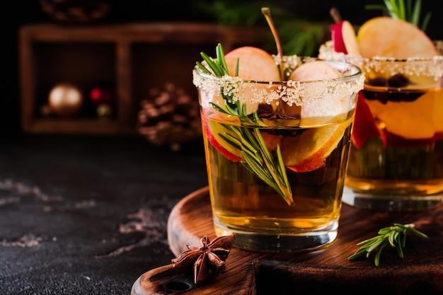 Tradycyjny świąteczny poncz jabłkowy z cynamonem, anyżem i gałązkami rozmarynu na ciemnym stole