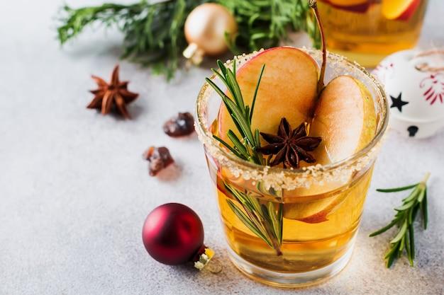Tradycyjny świąteczny poncz jabłkowy z cynamonem, anyżem i gałązkami rozmarynu na lekkim stole