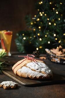 Tradycyjny świąteczny stollen na świątecznym stole z girlandą i wiecznie zielonymi gałązkami.