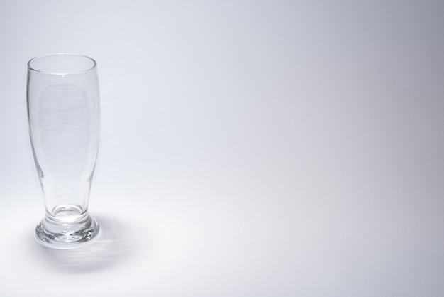 Tradycyjny szklany kubek na białym stole z copyspace