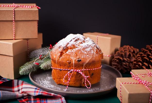 Tradycyjny tort świąteczny panettone z owocami i orzechami z dekoracją świąteczną
