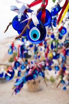 Tradycyjny turecki amulet nazar niebieskie oko z bliska wisi na drzewie z ozdobionymi kolorowymi wstążkami