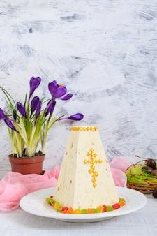Tradycyjny twaróg wielkanocny z kandyzowanymi owocami i czekoladowymi jajkami, wiosenne kwiaty krokusowe na jasnym tle wakacje.