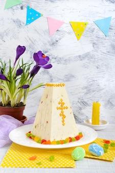 Tradycyjny twarogowy wielkanocny tort z kandyzowanymi owocami i wiosennymi kwiatami krokusy na wakacyjnym lekkim tle.