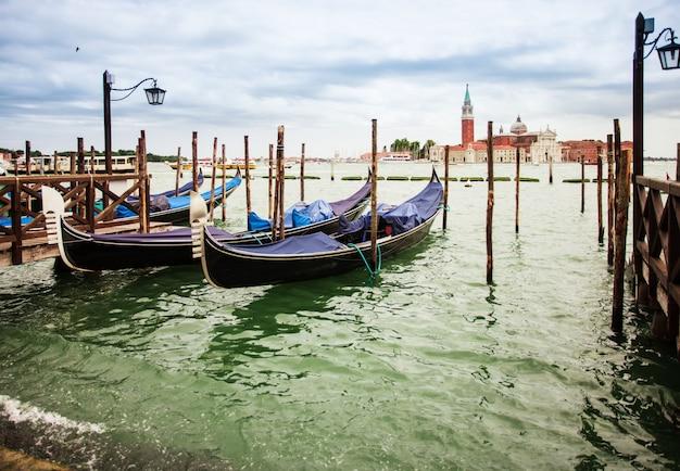 Tradycyjny widok z san marco, wenecja, włochy. niebieskie gondole zaparkowane na canal grande, w tle kościół san giorgio maggiore