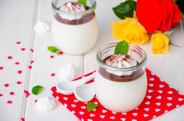 Tradycyjny włoski deser panna cotta z sosem czekoladowym i chrupiącą bezą, deser na walentynki serwowany w szklanych słoikach.