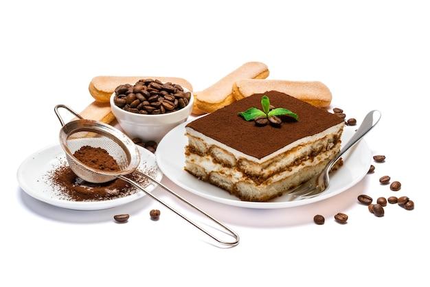 Tradycyjny włoski deser tiramisu część kwadratowa na płycie ceramicznej i ciasteczka savoiardi izolowane