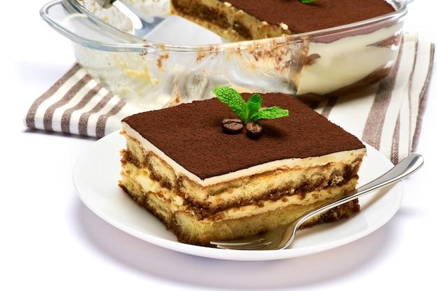 Tradycyjny włoski deser tiramisu w szklanej części naczynia do pieczenia na talerzu i łopatki na białym tle