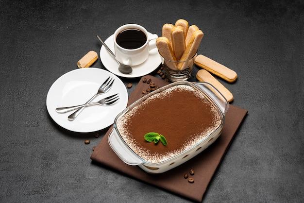 Tradycyjny włoski deser tiramisu w szklanym naczyniu do pieczenia, filiżankę świeżej gorącej kawy espresso i ciasteczka savoiardi na betonowym tle lub stole