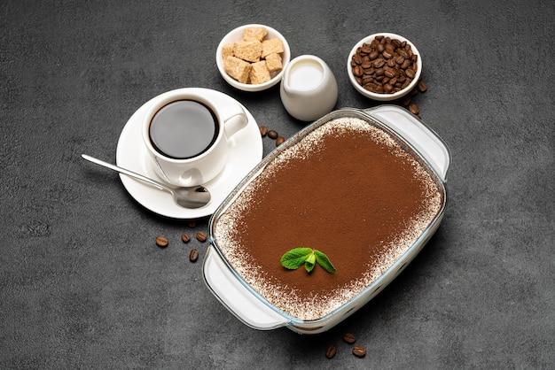Tradycyjny włoski deser tiramisu w szklanym naczyniu do pieczenia i filiżankę świeżej gorącej kawy espresso na betonowym tle lub stole