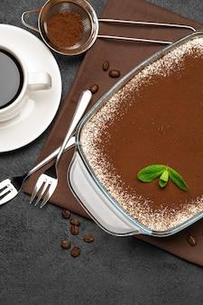 Tradycyjny włoski deser tiramisu w szklanym naczyniu do pieczenia i filiżankę świeżej gorącej kawy espresso na